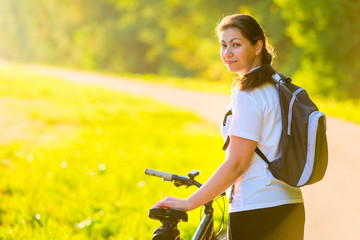 beautiful athlete with a backpack on a bicycle