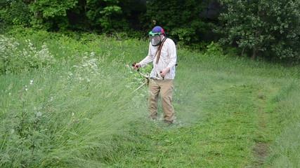 farmer worker man trim mow wet high grass after rain