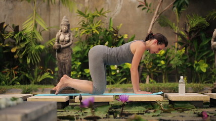 Young woman exercising, stretching on mat in exotic garden