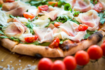 Pizza with cherry tomatoes, prosciutto and ruccola