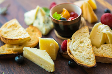 Assorted cheese on a wooden board.