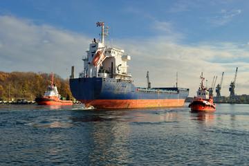 Statek w asyście holowników wpływa do portu