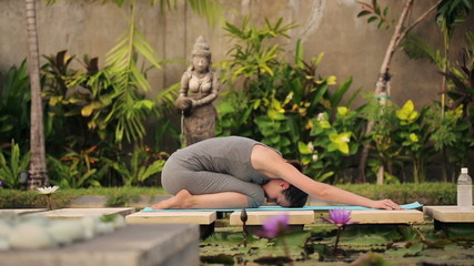 Woman doing japanese sit, stretching back in exotic garden