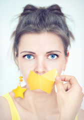 Portrait of a girl with blue eyes and yellow tape taped her mout