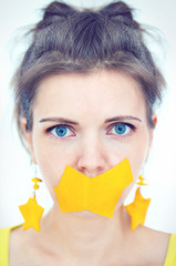 Portrait of a girl with blue eyes and yellow tape taped mouth cl