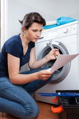 Woman trying to repair washing machine