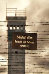 Wachturm mit Stacheldraht und Verbotsschild an der ehemaligen in