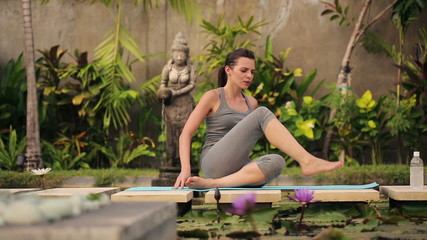 Attractive woman exercising, stretching in exotic garden