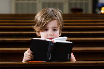 Junge liest im Gotteslob