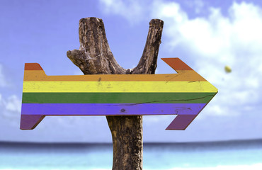 Rainbow wooden sign with a beach on background