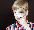 Portrait of a boy looking through the magnifying glass