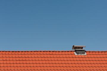 Ein neues Dach aus Tonziegeln mit Kaminabdeckung aus Edelstahl