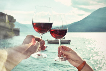 Two wineglasses in the hands against lake Como, Italy