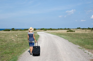 Woman walking away at a gravel road