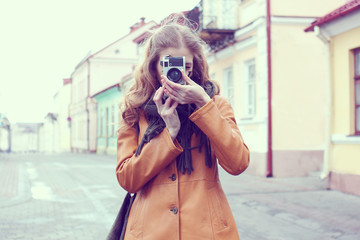 girl with an old camera walks through the streets