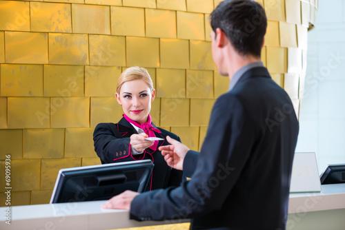 Rezeptionistin checkt Zgłoś uwagę lub komentarz do hasła Mann bei Anreise im Hotel ein