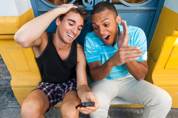 Young males having fun with a cellphone.