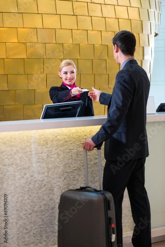 Rezeptionistin checkt Mann bei Anreise im Hotel ein - 69096109