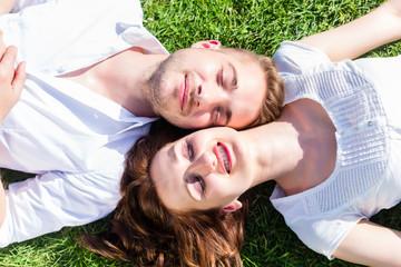 Paar liegt in Sonne auf Wiese