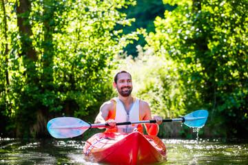 Mann fährt im Kajak auf Wald Fluss