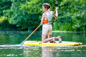 Frau beim Stehpaddeln Sup auf Fluss