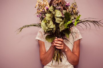 Young woman holding bouquet of dead flowers