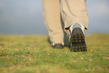 Back view of hiker legs walking on the mountain