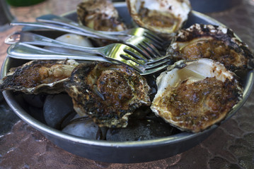 Garlic and butter oysters in the shell with forks