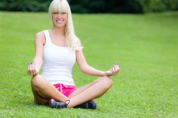 Hübsche Frau macht Yoga im Stadtpark