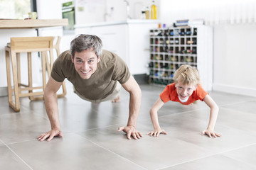 father and son  are doing pushups and having fun  at home