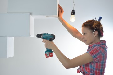 Beautiful young woman uses an electric drill
