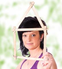 Frau hällt einen Zollstock als Hausgeformt