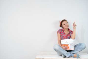 Young woman with paint bucket thinks over idea of repair
