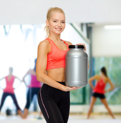 smiling sporty woman with jar of protein