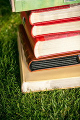 Stack of colored books lying on grass at sunny day