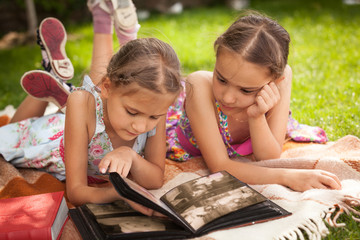 two little sisters looking photo album at park