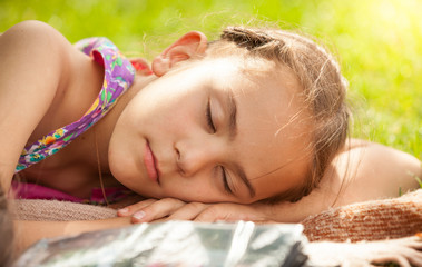 portrait of little girl sleeping on grass at park
