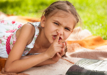 little girl lying at park and holding finger at lips