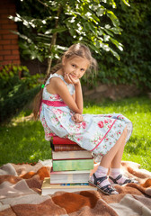 cute girl sitting on big stack of books at garden