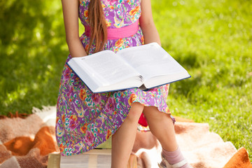girl in pink dress reading big book at park