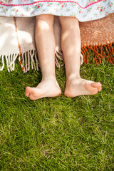 photo of girls feet on grass at sunny day