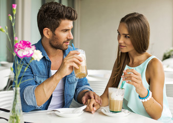 Young couple talking and drinking coffee