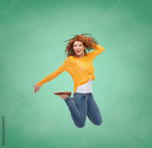 smiling young woman jumping in air - 69102177