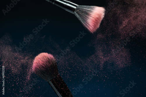 Professional black make-up brush with pink powder in motion isol - 69102328