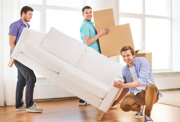 smiling friends with sofa and cardboard boxes