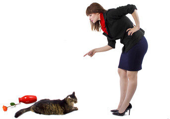 woman scolding pet cat that toppled a flower vase