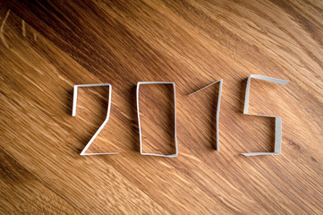 2015 Happy New Year paper digits on wood background.