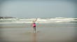 girl or teen learning to ride a skimboard on the Oregon coast