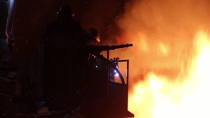Silhouette of firemen at fire with hose and heavy flames showing