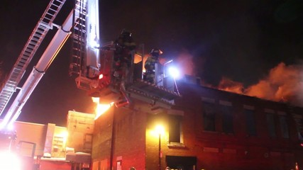Firemen in elevated basket rise above heavy flames